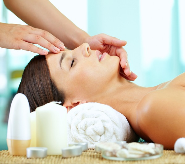 Female hands massaging young womanís face